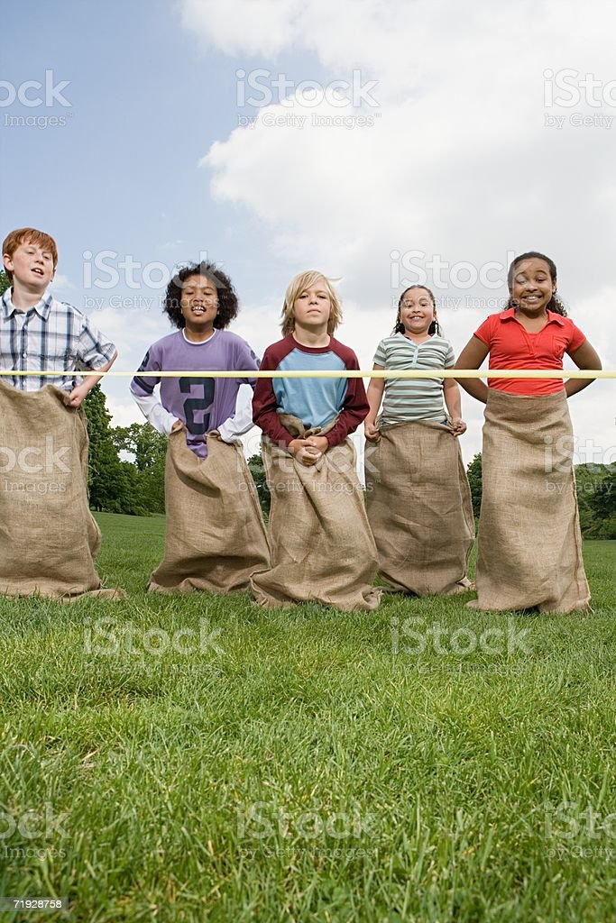 Kids near finish line in sack race stock photo