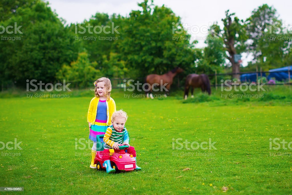 Kids on a farm with horses stock photo