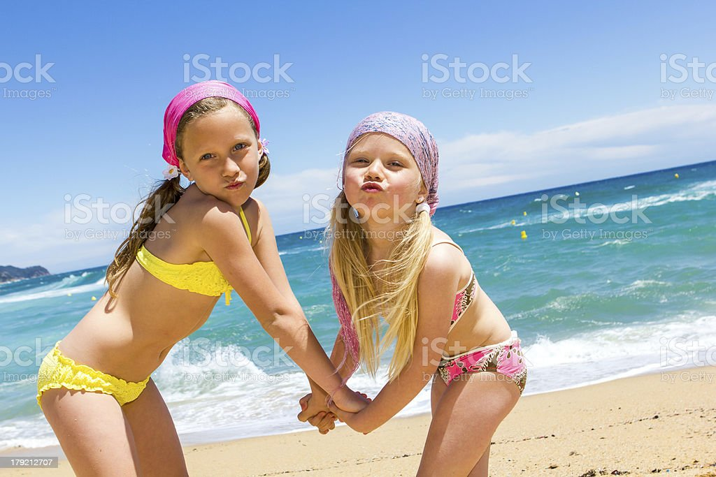 Drôle enfants sur la plage en tirant des visages. photo libre de droits