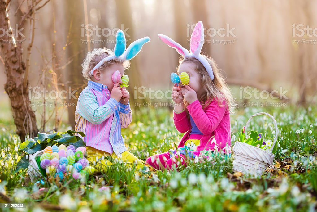 Kids on Easter egg hunt in blooming spring garden stock photo