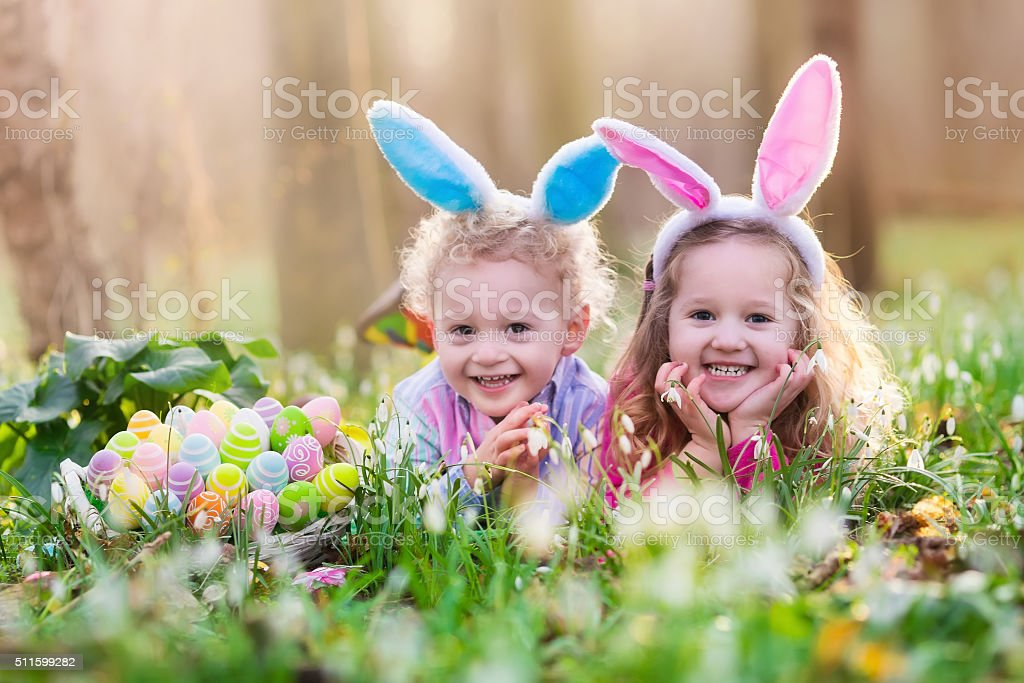 Kids on Easter egg hunt in blooming spring garden stock photo