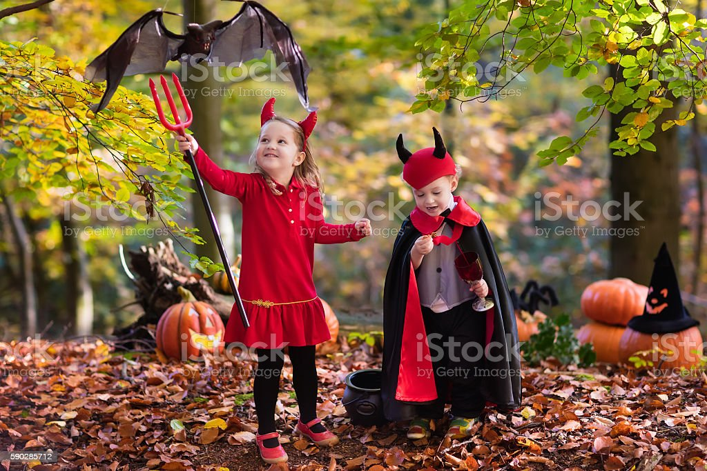 Kids on Halloween trick or treat in autumn forest stock photo