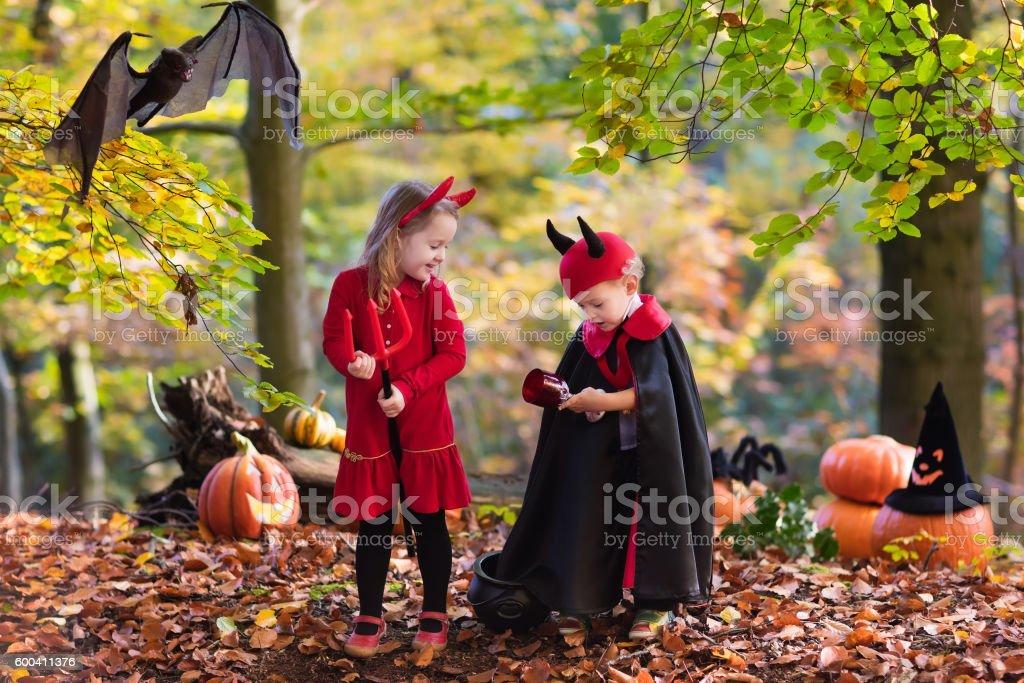 Kids on Halloween wearing devil and vampire costume stock photo