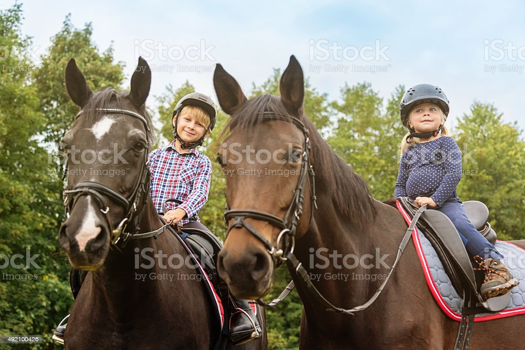 Kids on Horses Brother and Sister Horseback Riding stock photo