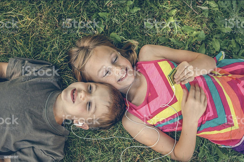 kids on lawn sharing headphones listening to MP3 Player stock photo