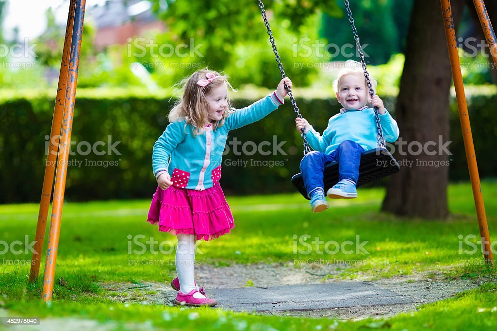 Kids on playground swing stock photo