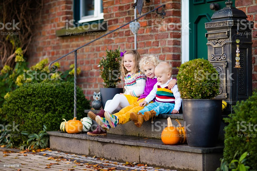 Kids on stone stairs at house porch on autumn day stock photo