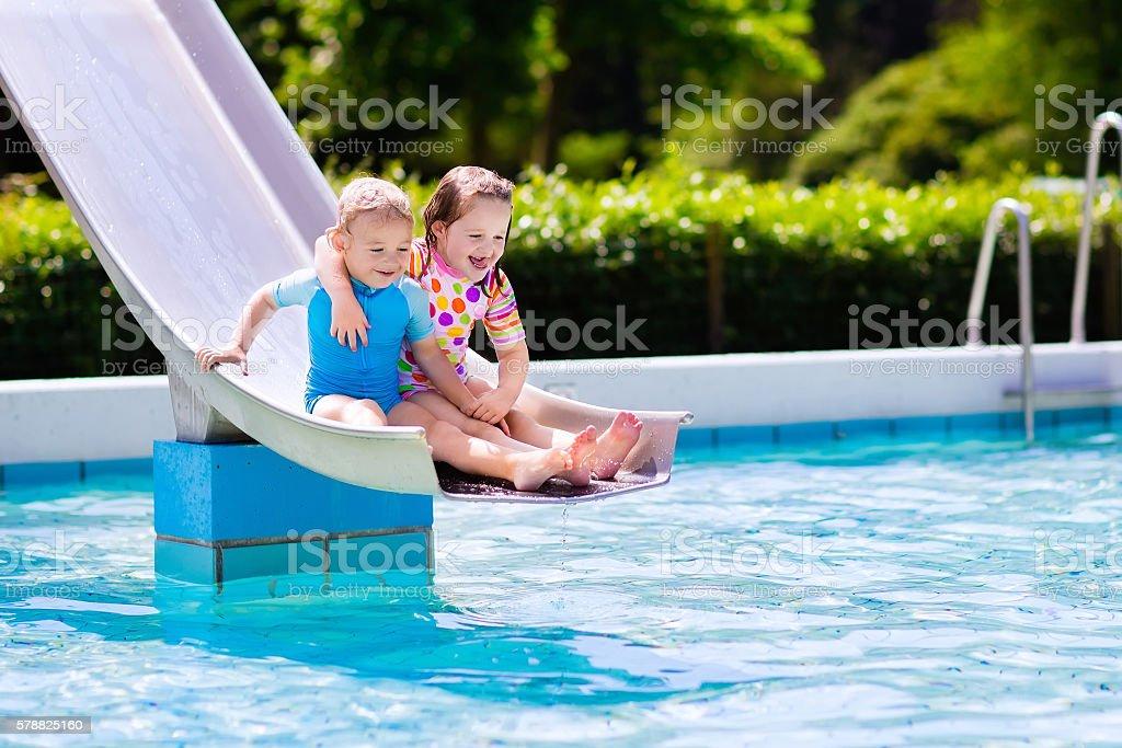 Kids on water slide in swimming pool stock photo