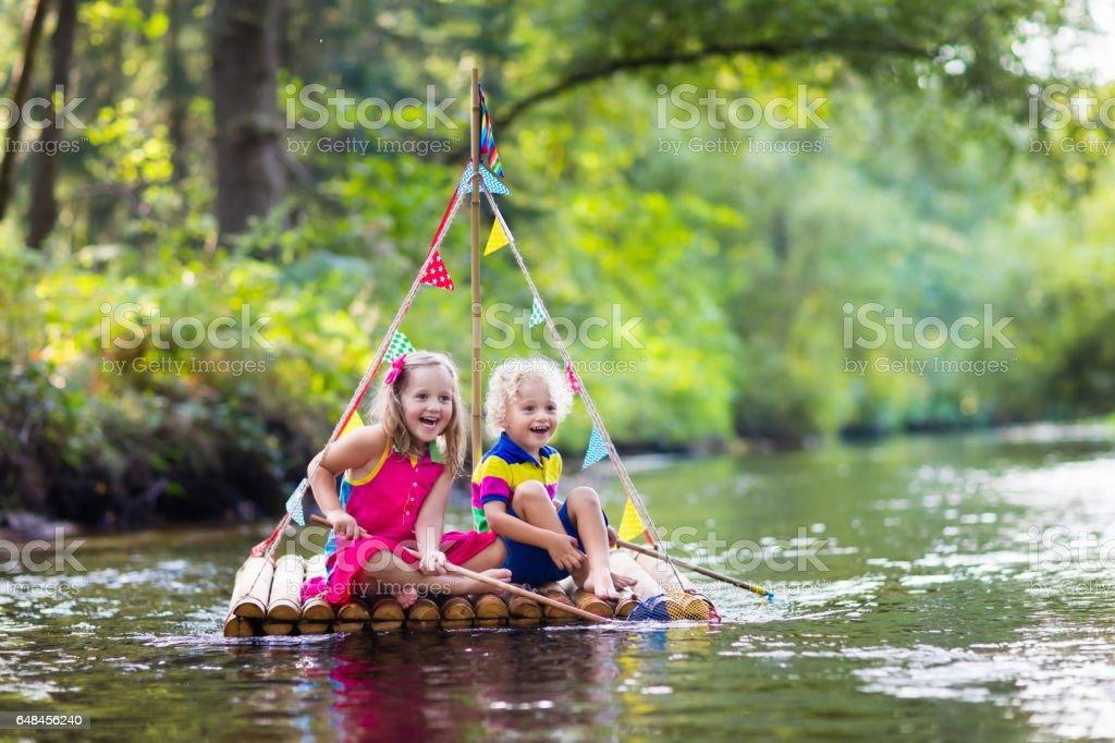 Kids on wooden raft stock photo