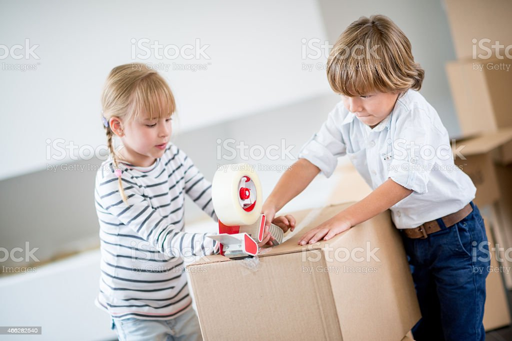 Kids packing and closing boxes with tape gun stock photo