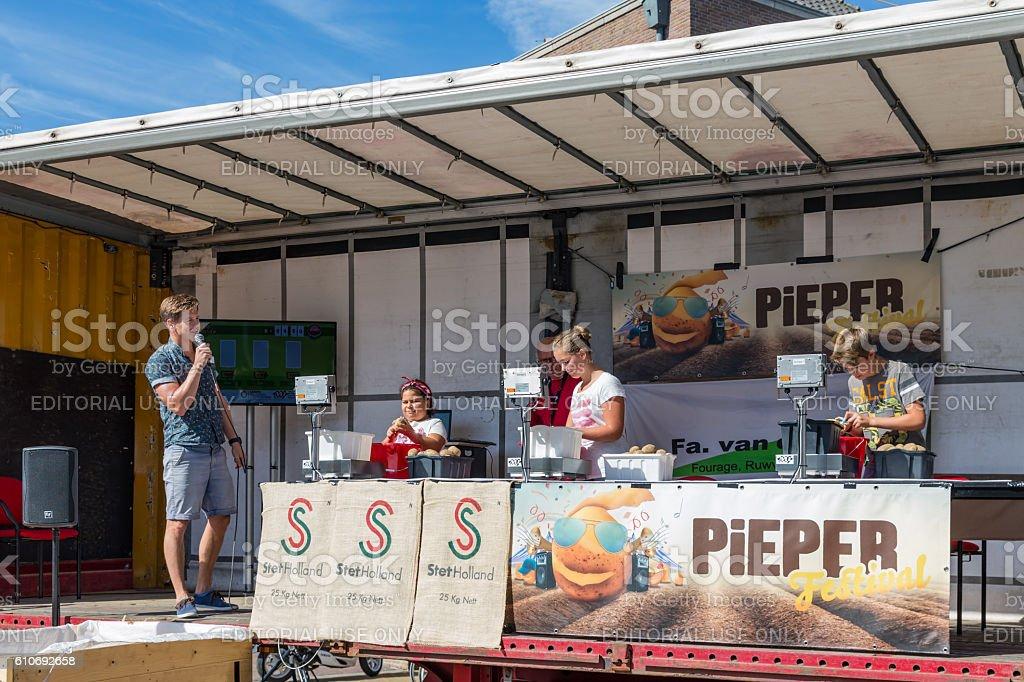 Kids peeling potatoes at a Dutch agricultural potato festival stock photo