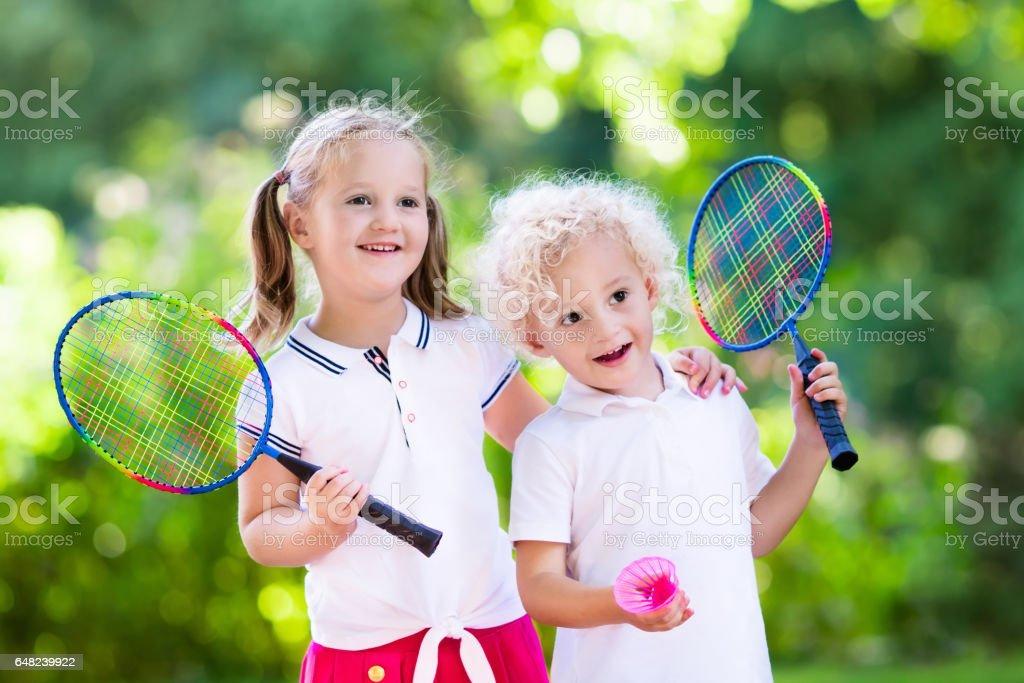 Kids play badminton or tennis in outdoor court stock photo