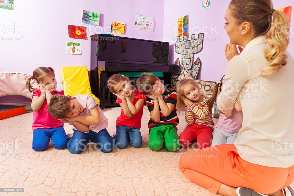 Kids play game pretending be asleep with teacher stock photo