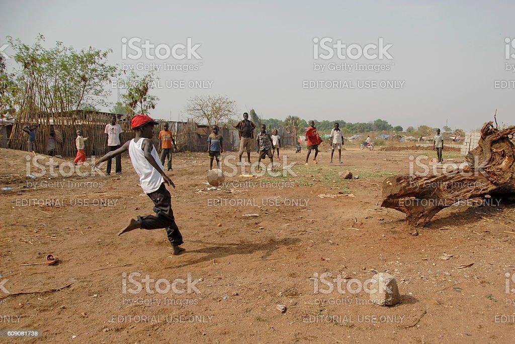 Kids play soccer on a street in Juba, South Sudan. stock photo