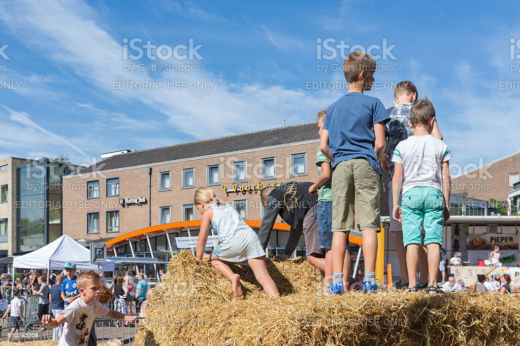 Kids playing at hay bales on Dutch agricultural potato festival stock photo