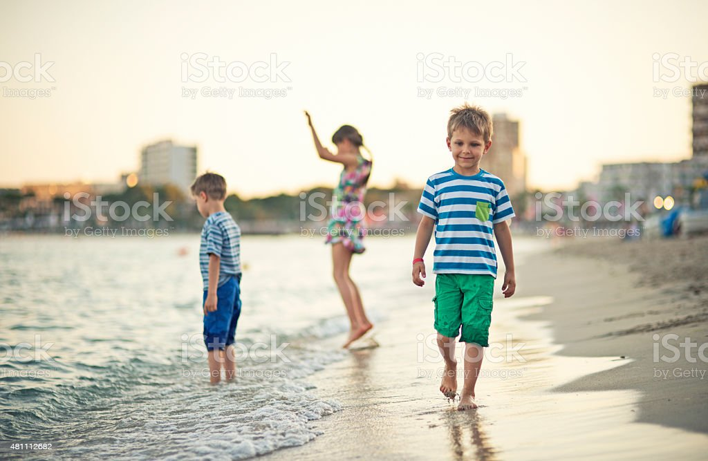 Kids playing at the beach at evening stock photo