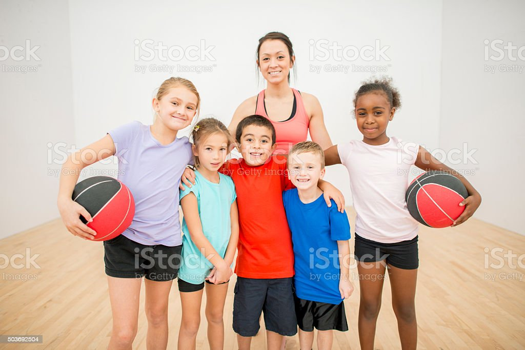 Kids Playing Basketball at the Gym stock photo