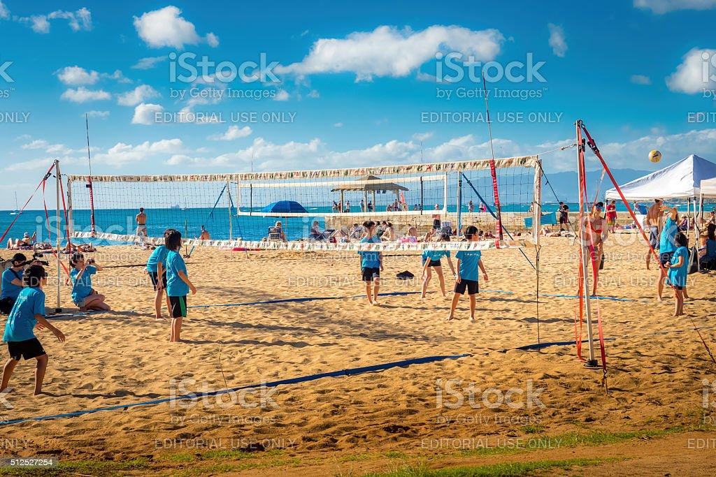 Kids playing beach volleyball, Waikiki Beach Area. stock photo