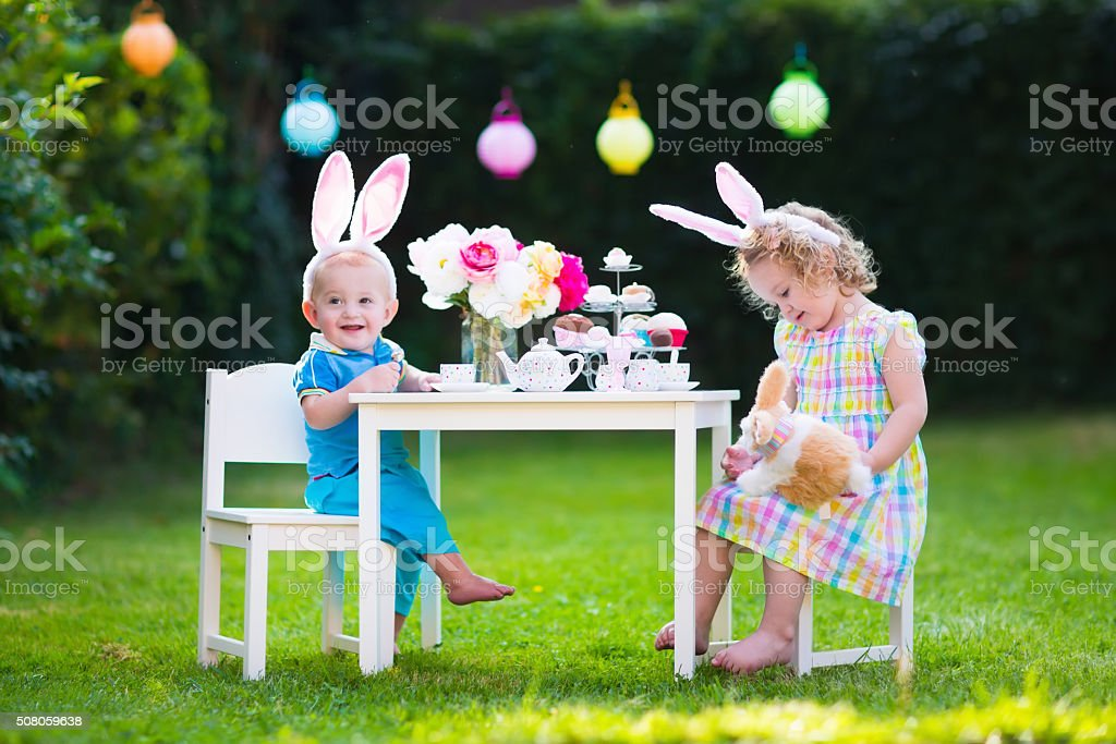 Kids playing Easter tea party with toys stock photo