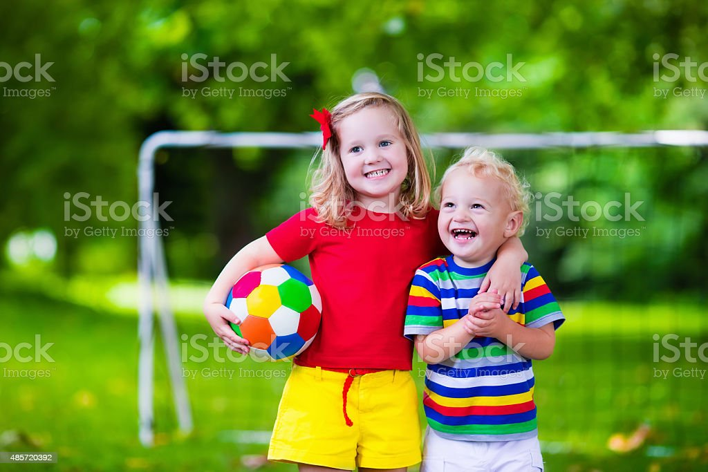 Kids playing football in a park stock photo