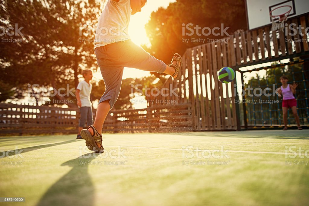Kids playing football in the schoolyard stock photo