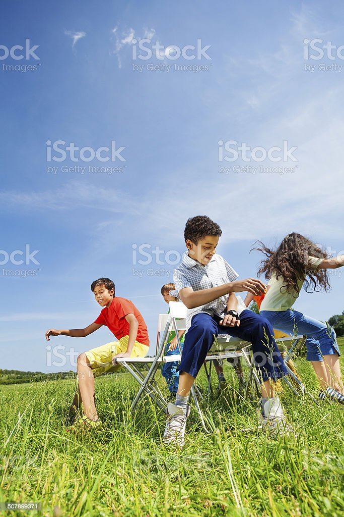 Kids playing game and sit fast on chairs outside stock photo