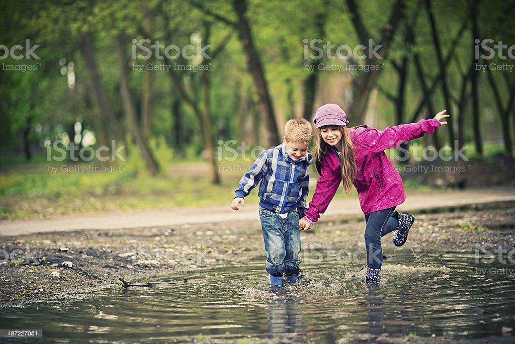 Kids playing in a puddle stock photo