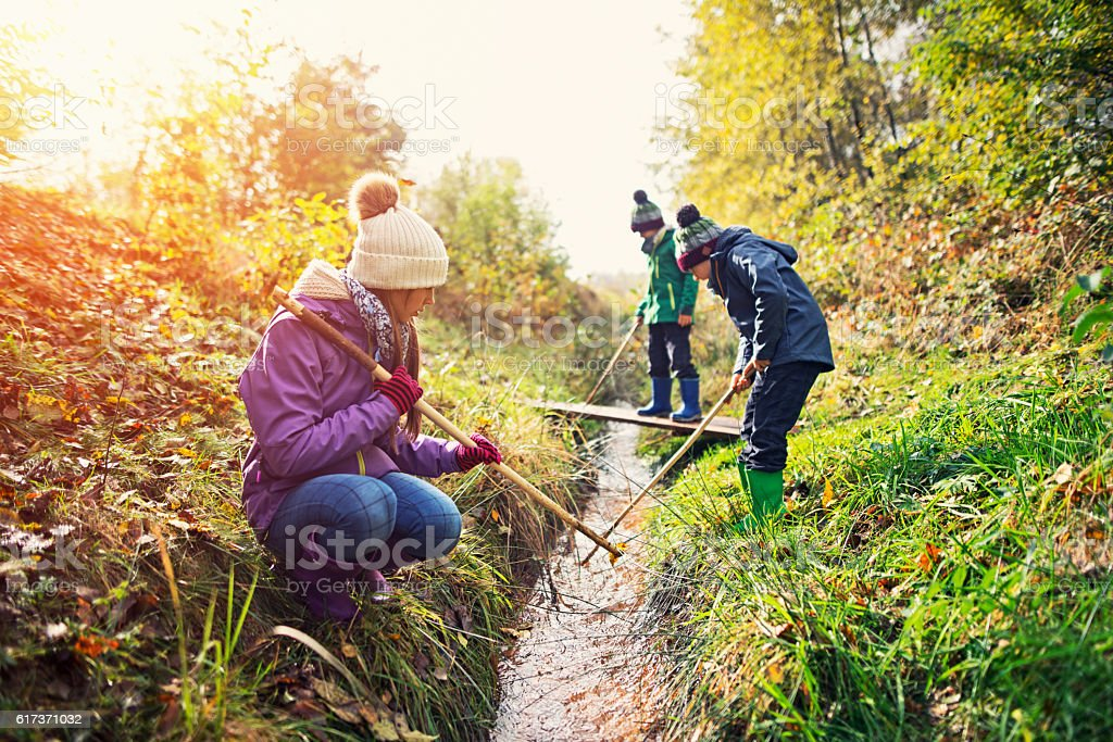 Kids playing in a small stream on sunny autumn day. stock photo
