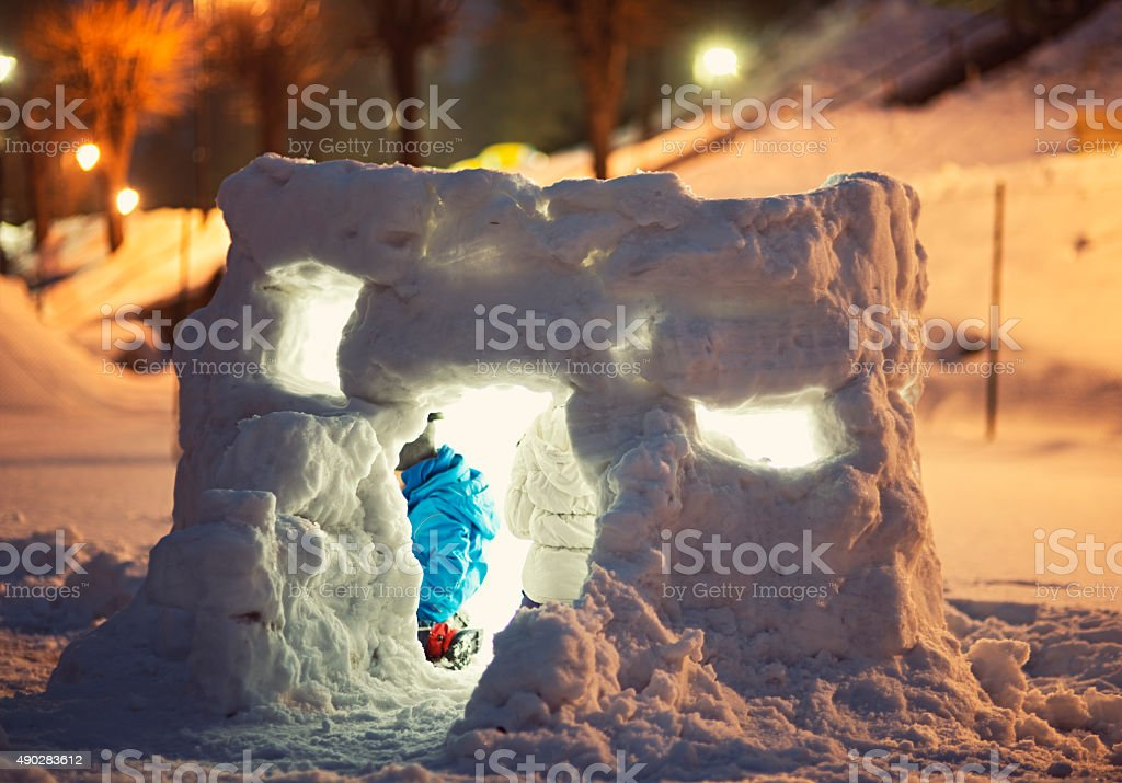 Kids playing in a snow hut stock photo