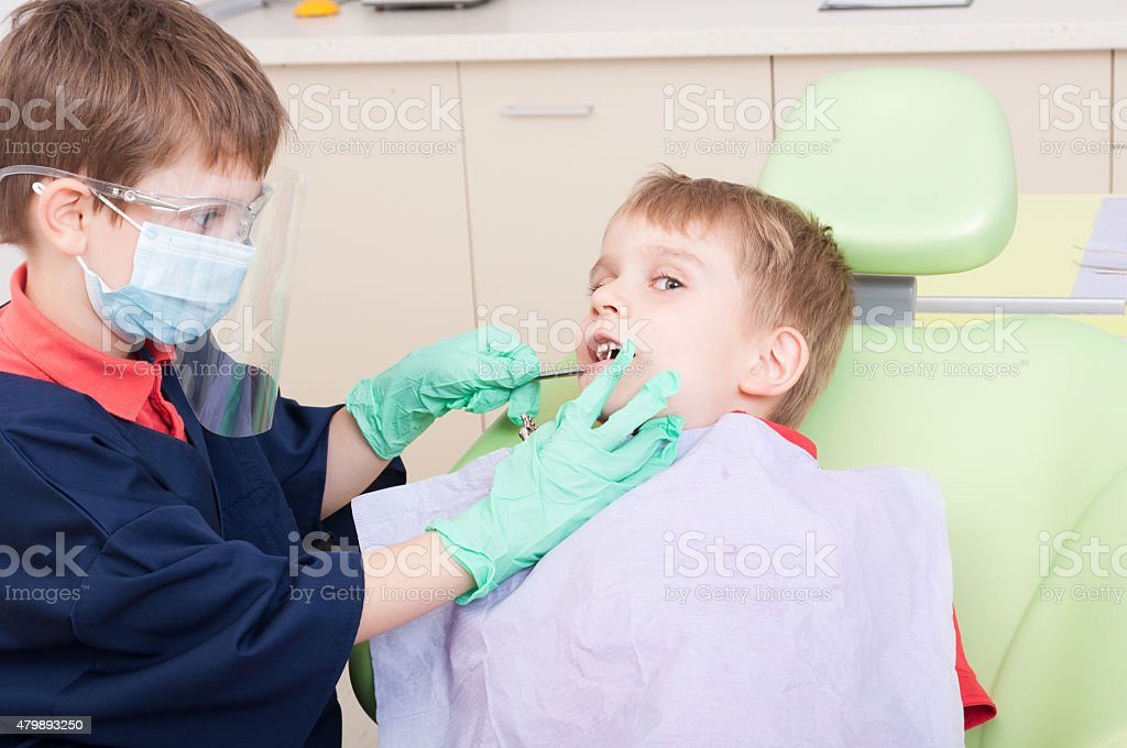 Kids playing in dentist office as doctor and patient stock photo