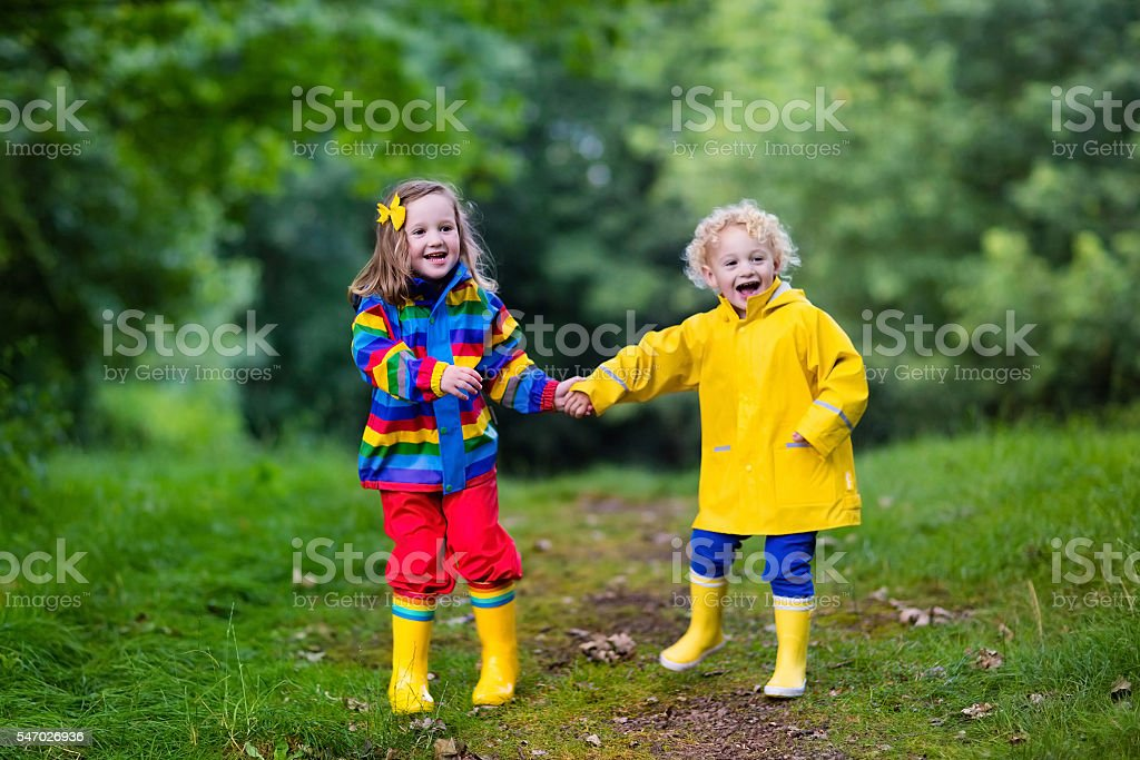 Kids playing  in rainy summer park stock photo