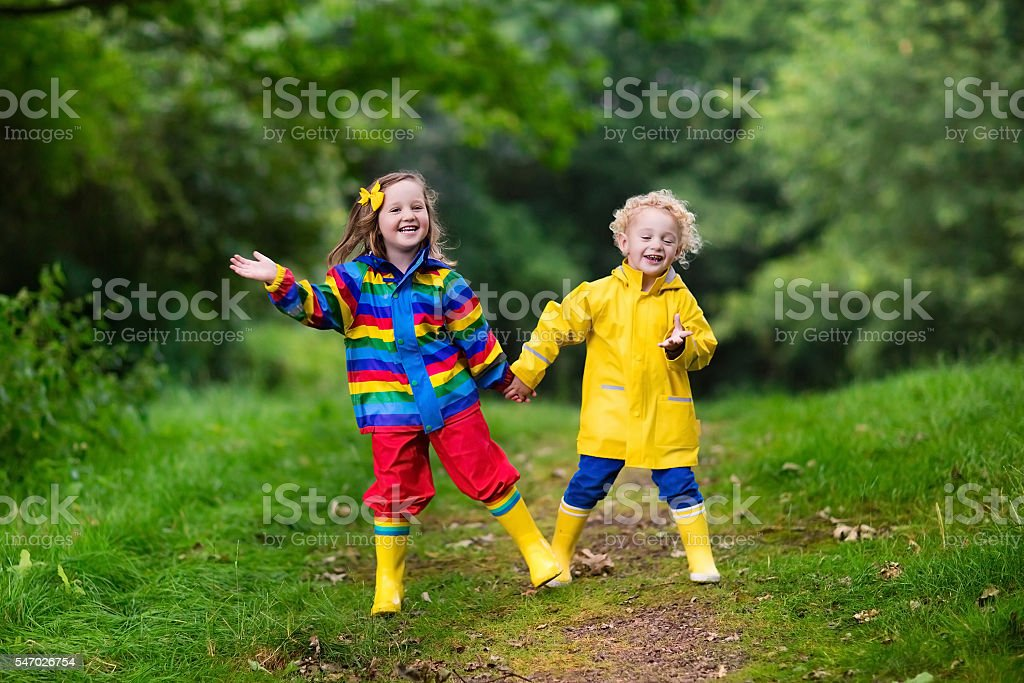 Kids playing in the autumn rain stock photo