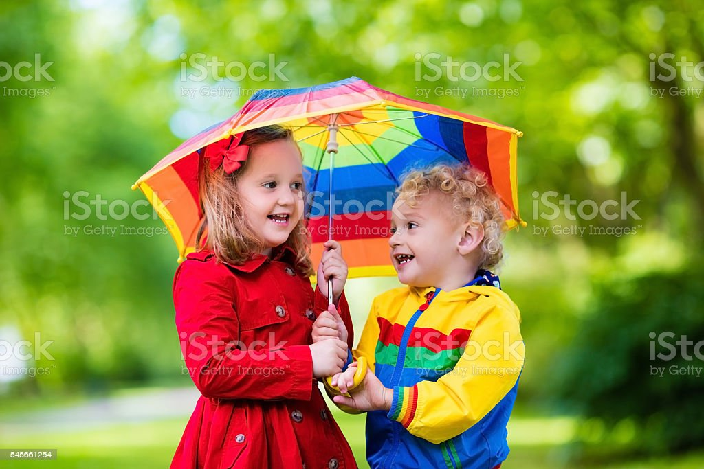 Kids playing in the rain under colorful umbrella stock photo