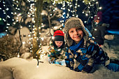 Kids playing in the snowy winter garden under christmas tree