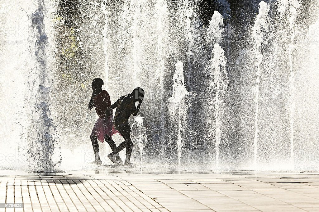 Kids playing in water jets stock photo