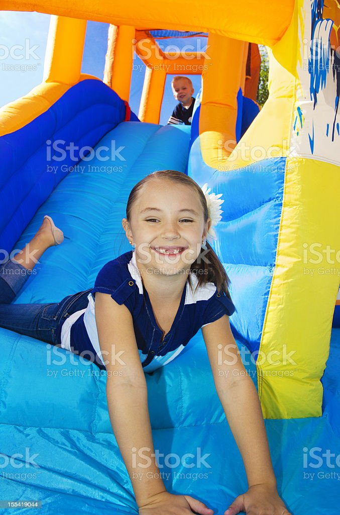 Kids playing on an inflatable slide bounce house stock photo