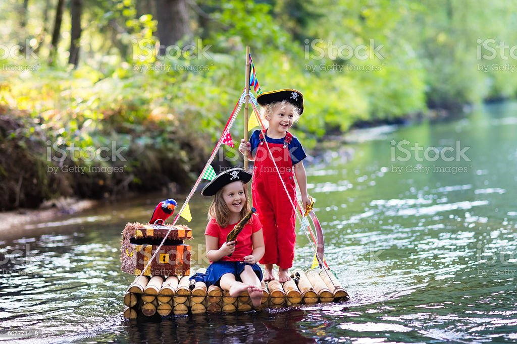 Kids playing pirate adventure on wooden raft on hot day stock photo