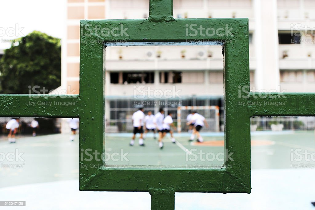 Kids playing soccer at schoolyard stock photo