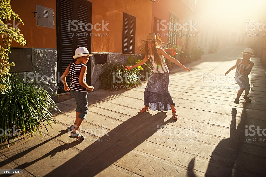 Kids playing tag in mediterranean street. stock photo