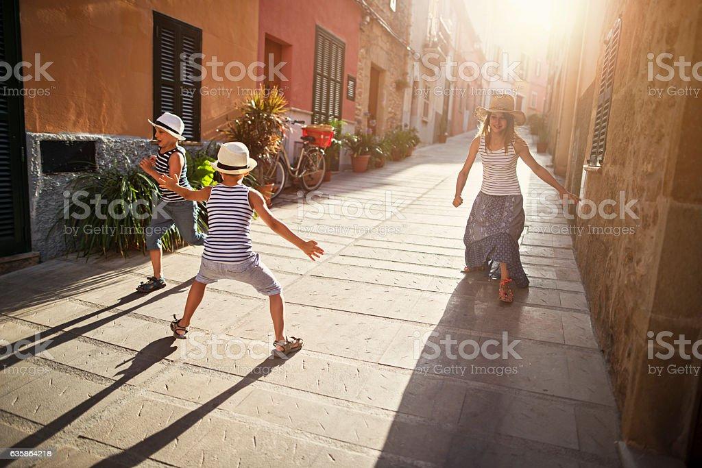 Kids playing tag in mediterranean street. stock photo