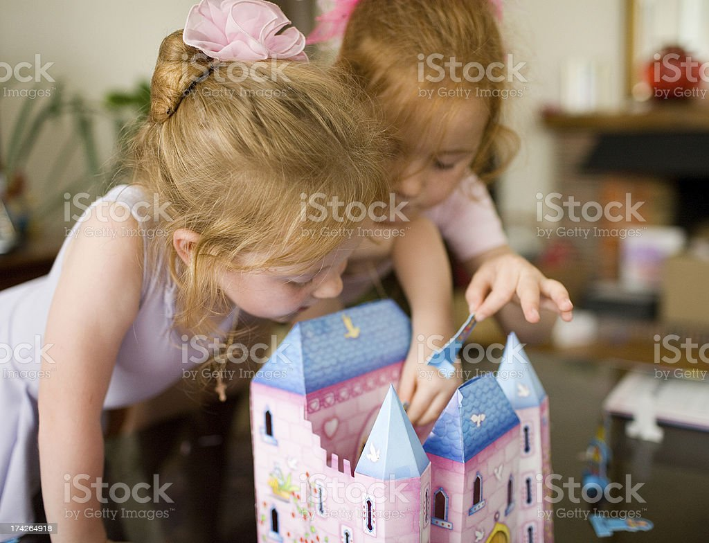 Kids playing together with doll house stock photo