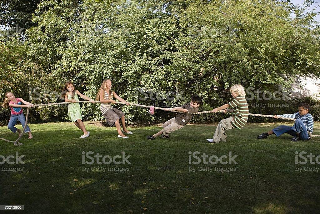 Kids playing tug of war royalty-free stock photo