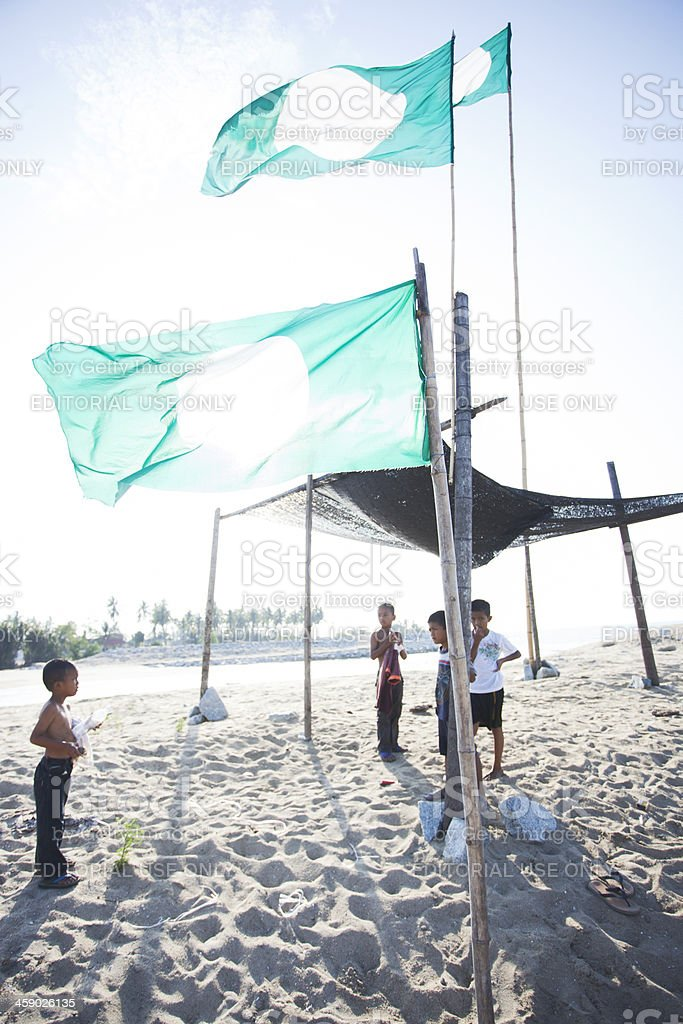 Kid's playing under Islamic party's flag. stock photo