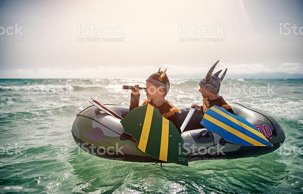 Kids playing vikings at sea on a boat stock photo