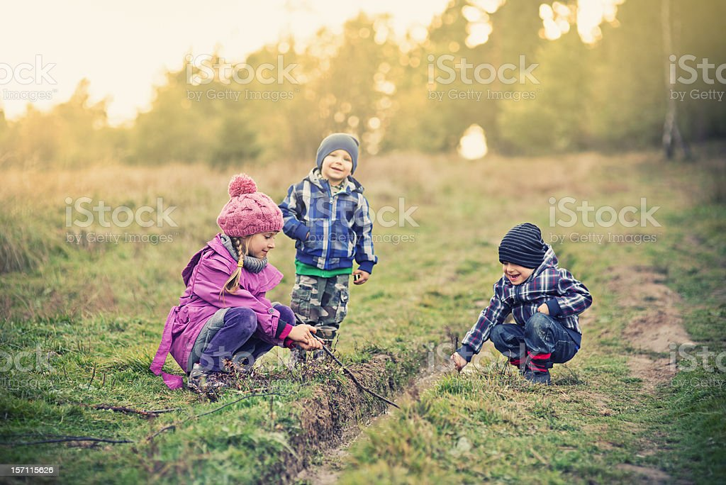 Kids playing with a puddle royalty-free stock photo