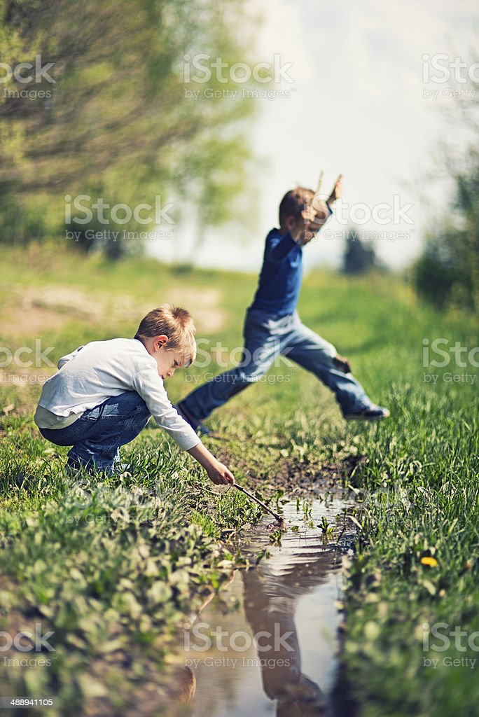 Kids playing with a puddle stock photo