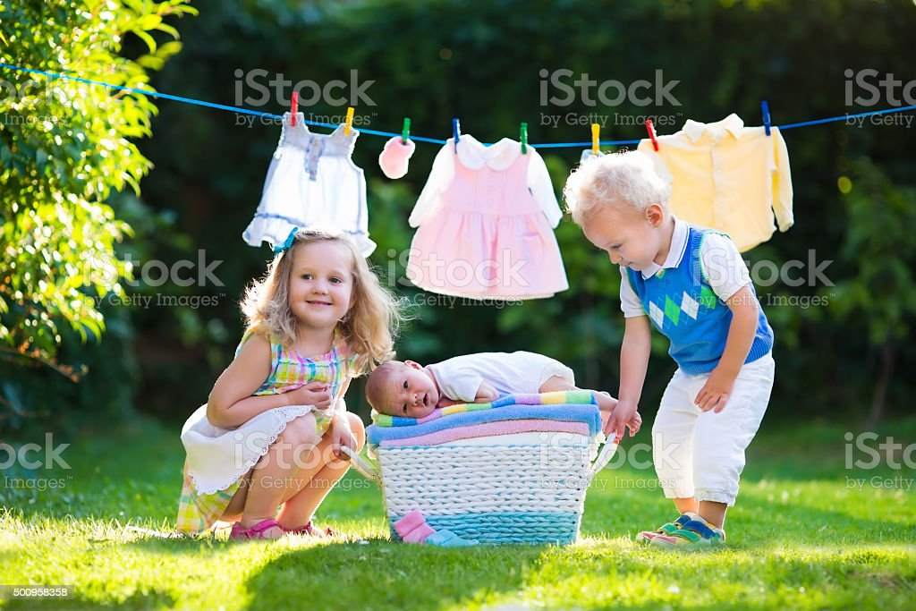 Kids playing with newborn baby brother stock photo