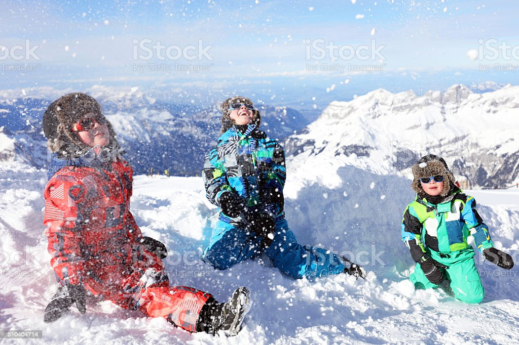 Kids Playing with Snow in Swiss Mountains in Winter stock photo