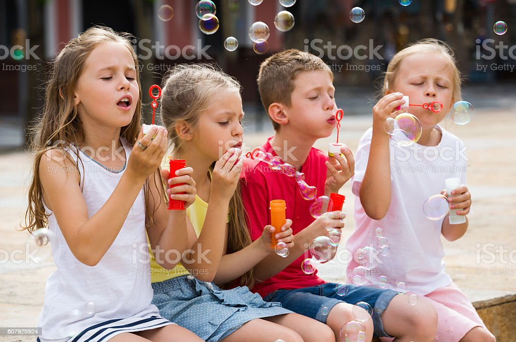 Kids playing with soap bubbles stock photo