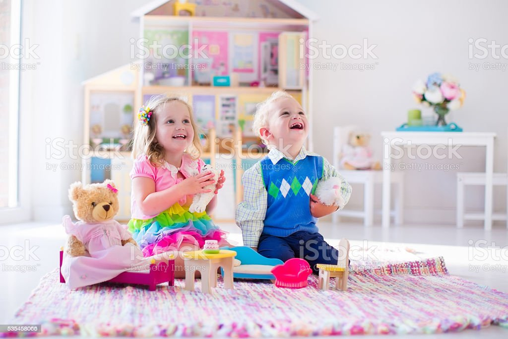 Kids playing with stuffed animals and doll house stock photo